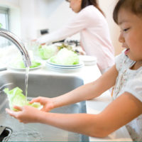 Young girl safely rinsing lettuce under cool water to prevent scalding burn injury.