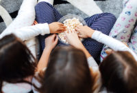 Overhead shot of three grade-school aged girls wearing pajamas sharing a bowl of popcorn at a sleepver.