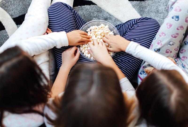 Overhead shot of three grade-school aged girls wearing pajamas sharing a bowl of popcorn at a sleepver.