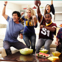 Group of friends in a living room getting excited about a football game on TV