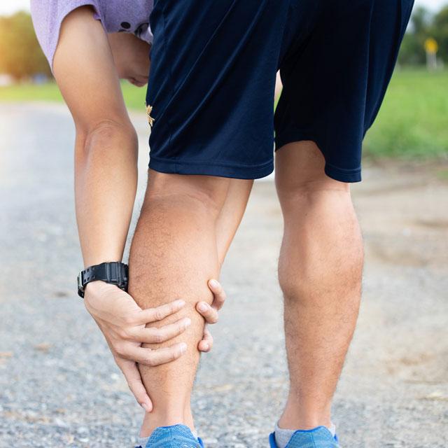 Runner massaging pain in leg. Consider PAD treatment.