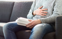 Man sitting on couch after eating a meal feeling for constant heartburn.