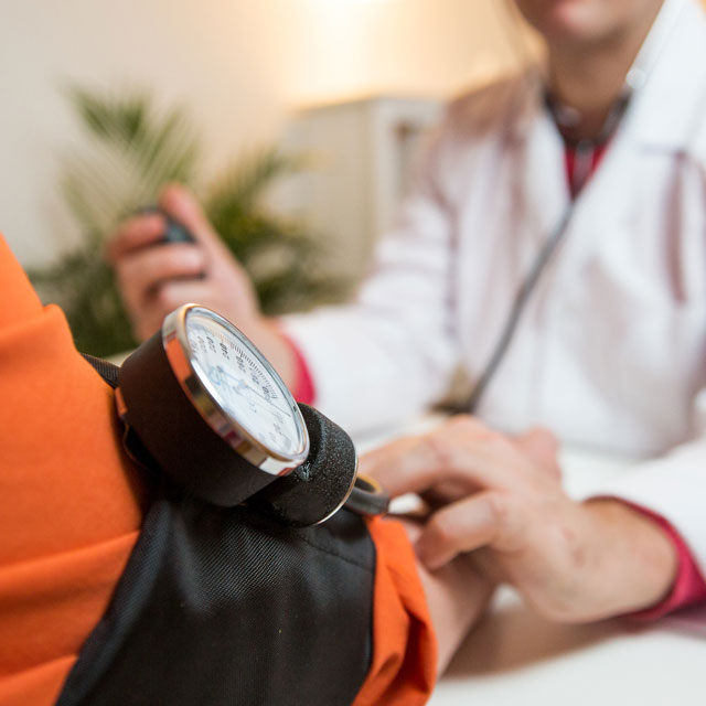 Nurse checking patient's blood pressure to catch early warning signs of stroke.