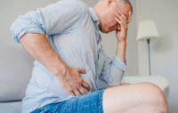 Man suffering from fatty liver disease and clutching stomach.