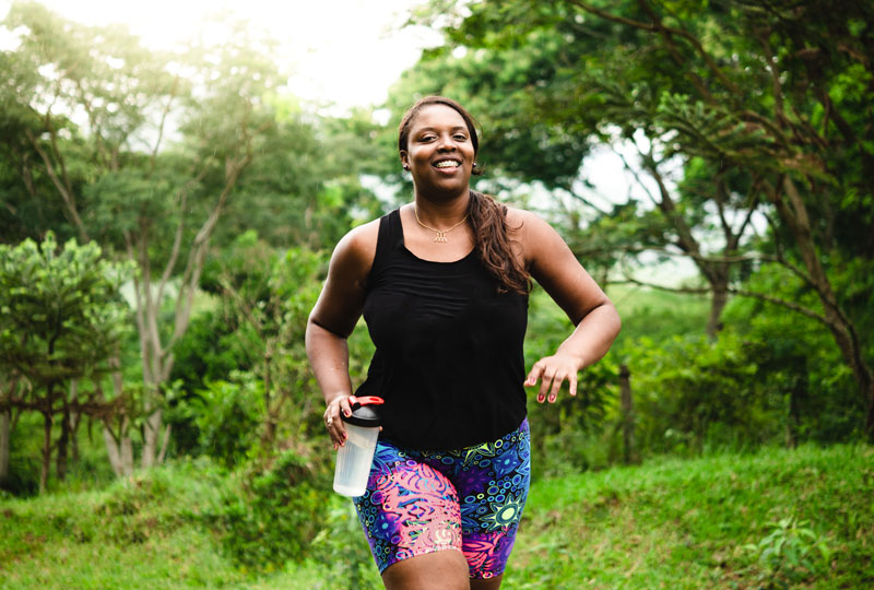 Woman jogging outdoors carrying a water bottle.