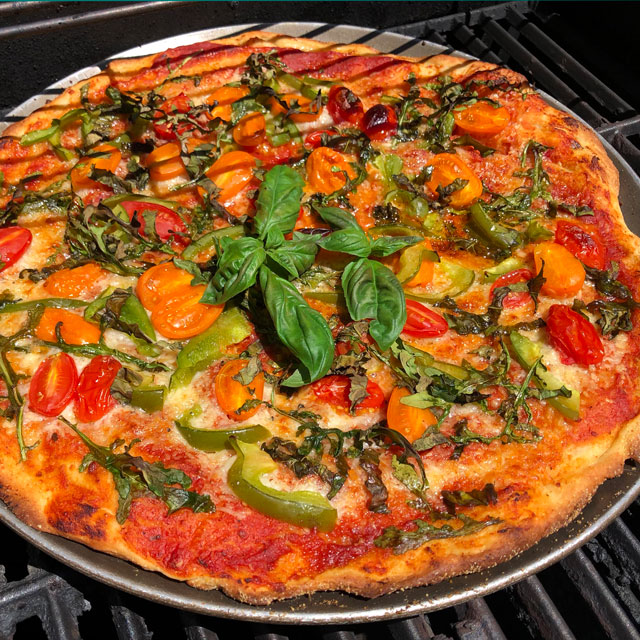 Grilled pizza topped with fresh vegetables and herbs.