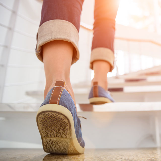 Image of woman walking and avoiding a sedentary lifestyle.