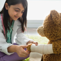 A young girl practices being a doctor by wrapping a teddy bear's limb in a bandage.