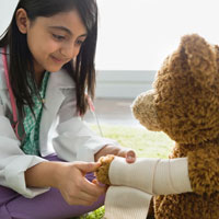 A young girl wraps a bandage around a teddy bear's arm.