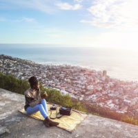 A woman sits on an overlook with the view below of a large city she has traveled to.