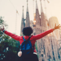 Following healthy travel tips can lead to happy travel experience like this woman posing in front of a cathedral in Spain.