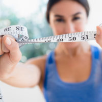 Woman holds up tape measure in foreground. Thumbnail sized image.