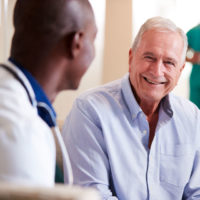 Older patient utilizing Medicare wellness exam to speak with doctor.