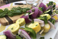 Closeup of raw vegetables threaded on skewers, ready to grill.