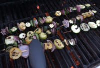 Skewered vegetables cooking on a grill.