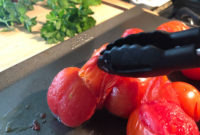 Lightly roasted whole tomatoes on a baking sheet; tongs are peeling them