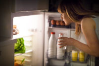 Woman looking into fridge looking for better alternatives to stop snacking at night.