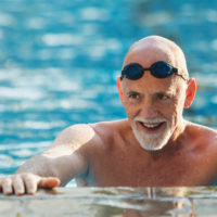 A smiling older man stands in chest-deep water at the edge of a swimming pool.