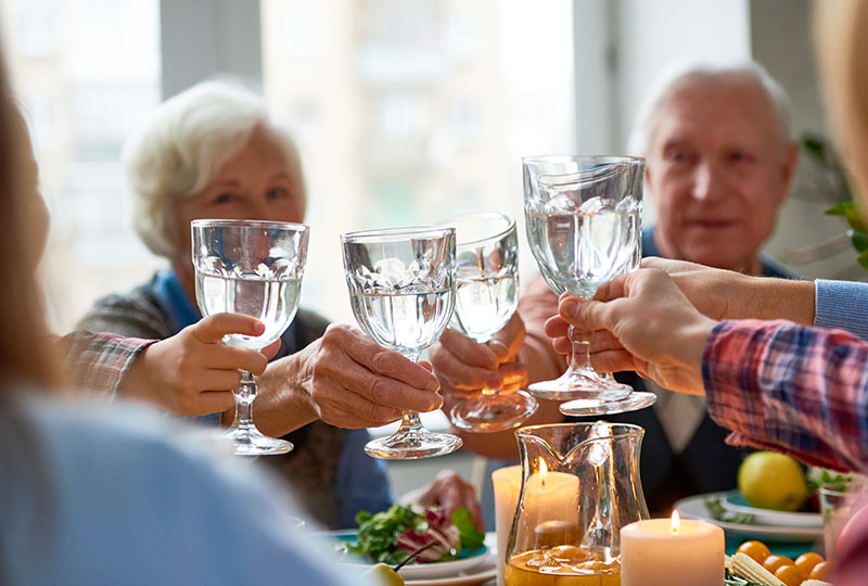 A family raises glasses of water in a toast to begin a meal.