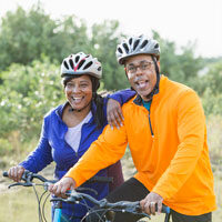 Small-size photo, a couple in bike helmets standing outdoors with their bikes.