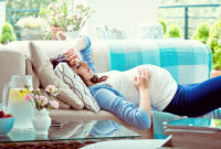 Woman laying on couch feeling discomfort during pregnancy.