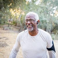 Older African American man walking outdoors wearing earbuds