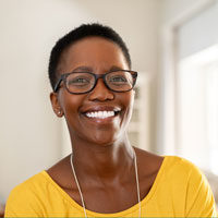 Smiling African American woman in glasses and bright yellow top