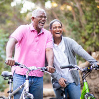 Older African-American couple stand on a path with bicycles
