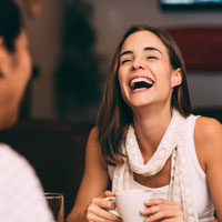 Young woman laughs with a friend.