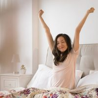 Woman stretches while sitting up in bed.