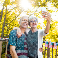 A middle-aged couple take a selfie standing outdoors on a deck in autumn.